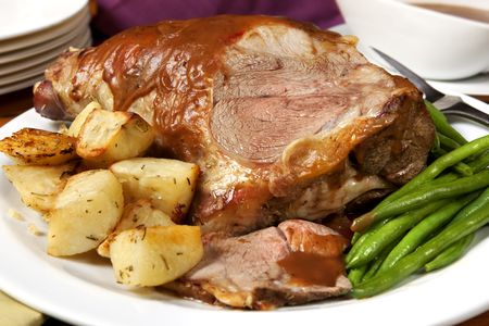 roast meat: Roast leg of lamb, with string beans, roasted potatoes, and gravy.  Delicious! Stock Photo