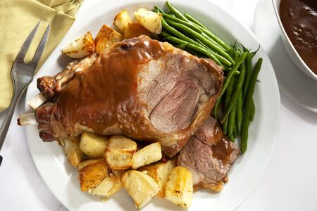 gravy: Roast leg of lamb on a serving platter, with potatoes, beans, and gravy. Stock Photo
