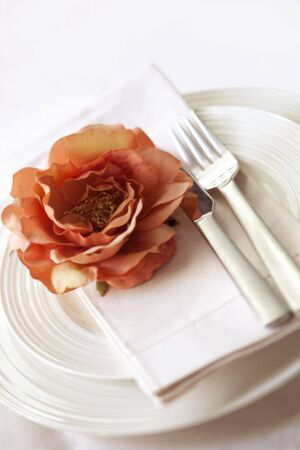 Place setting in soft focus, with delicate peach flower. photo