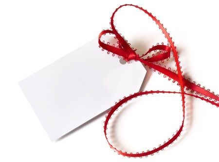 Blank white gift tag tied with fancy red ribbon.  Over white background. Stock Photo - 6196716
