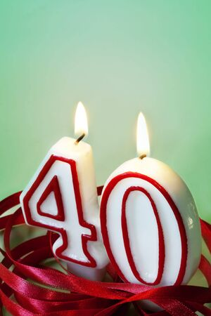 Number 40 candles, surrounded by red ribbon.  40th birthday or anniversary. Stock Photo - 6291248