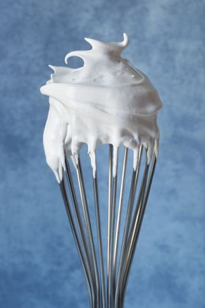 wire whisk: Meringue on a wire whisk, over blurred blue background.  Perfect pavlova in the making!