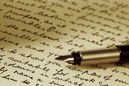 Vulpen over pagina van ouderwetse handschrift script.  Sepia toon. Stockfoto