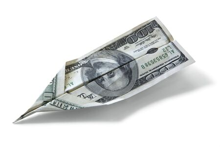 American one hundred dollar bill folded into an airplane, casting shadow over white. photo