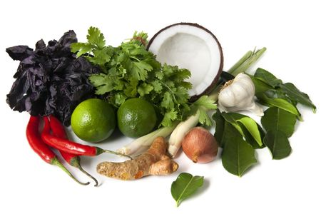 Ingredients for Thai food, ready for cooking.  Includes purple basil, coriander or cilantro, coconut, lemon grass, garlic, kaffir lime leaves, shallots, limes, red chilli peppers, and galangal.   photo