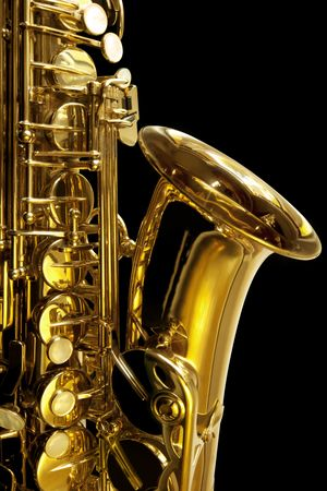 brass: Detail of alto saxaphone, over black background.