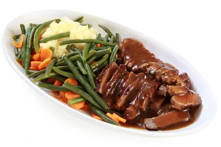 gravy: Serving platter of sliced roast beef and gravy, with vegetables.  Isolated on white.