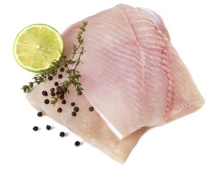 whitefish: Raw fish fillet with lime and thyme, ready for cooking.