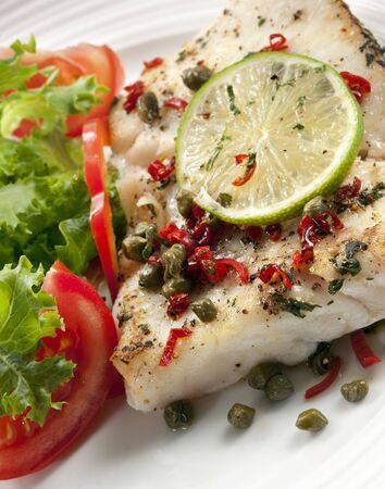 alcaparras: Filete de pescado blanco a la parrilla con una ensalada. Decorado con alcaparras, chili y cal.