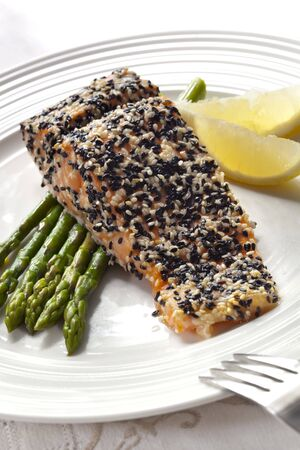 white sesame seeds: A salmon fillet baked with a crust of black and white sesame seeds, served with asparagus and lemon wedges.  Delicious, simple and healthy. Stock Photo