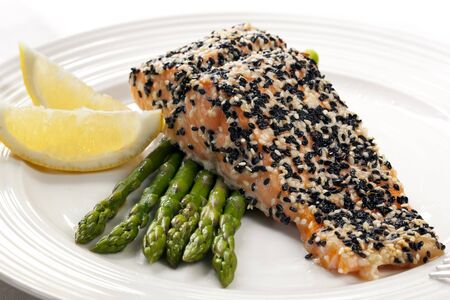 white sesame seeds: Perfect salmon fillet baked with a crust of black and white sesame seeds.  Served with fresh asparagus. Stock Photo