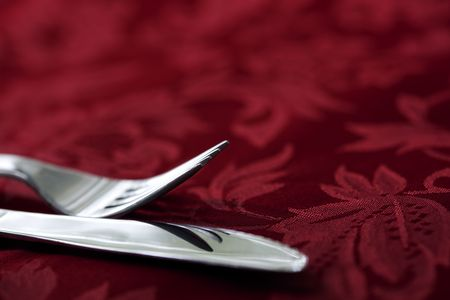 talher: Silver knife and fork on red damask linen tablecloth.  Focus on fork tines.