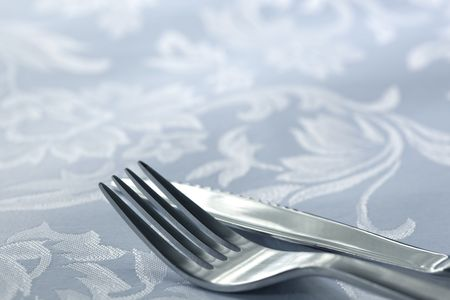 tine: Silver knife and fork on white damask linen tablecloth.  Shallow depth of field, with focus on fork tine.  Lots of copy-space.