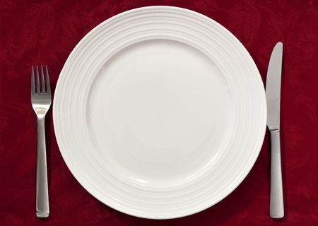 table linen: Place setting on red damask tablecloth.  Silverware and dinner plate. Stock Photo