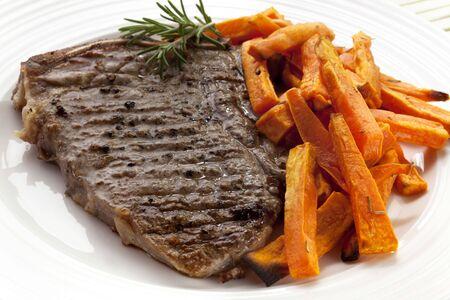 t bone steak: Grilled T-bone steak with oven-baked sweet potato fries.  Stock Photo