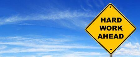 hard work ahead: Road sign warning of hard work ahead, against panoramic blue sky.