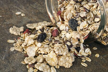 sultanas: Muesli spilling from a storage jar, onto stone bench.  Delicious granola mix of grains and dried fruit.