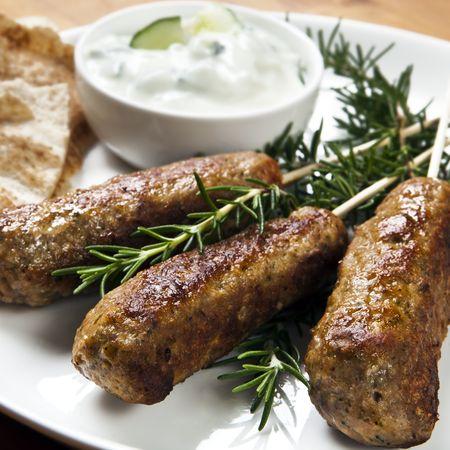 lebanese food: Lamb kofta served with cucumber yogurt and flat bread. Stock Photo