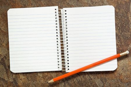 Two pages of open spiral notebook, with a pencil, over stone textured background. Stock Photo - 6789286