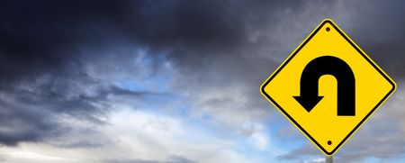 u turn sign: U turn road sign against storm clouds.  Time to change direction.