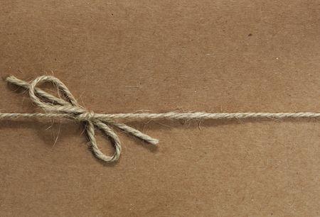 Chaîne liée dans un salut, sur papier recyclé brun.  Beaucoup de textures dans les ficelles et le papier.