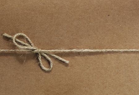 string: String tied in a bow, over brown recycled paper.  Great textures in the twine and paper.