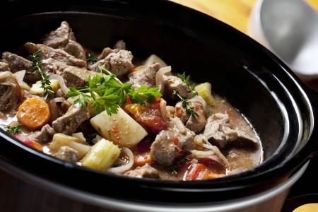 Rund vlees stoof pot in een slow-fornuis, klaar om te serveren.  Stockfoto