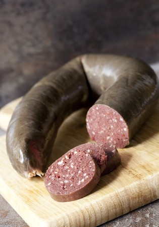 animal blood: Black pudding, with cut slices, on chopping board over stone background. Stock Photo
