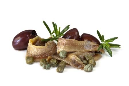 pitted: Filetti di acciughe con capperi di bambino, snocciolato olive nere e rosmarino, isolated on white. Archivio Fotografico