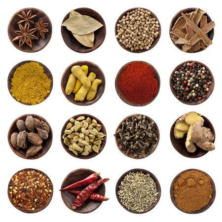 Collection of spices in small wooden bowls, isolated on white. From top left: Star anise, bay leaves, coriander seeds, cinnamon bark, curry powder, turmeric fingers, paprika, peppercorns, black cardamom pods, cardamom seeds, cloves, ginger root, chili fla photo