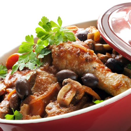 Traditional chicken cacciatore, in a red casserole dish. Stock Photo