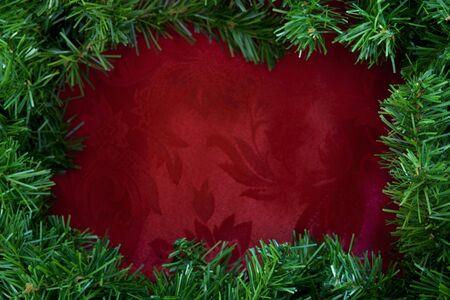 christmas garland: Christmas garland border over rich red brocade fabric.  Lots of copy-space. Stock Photo