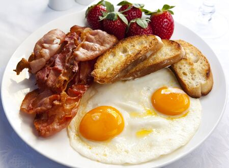 Bacon and eggs, with toasted croutons and strawberries.  A delicious breakfast. Stock Photo