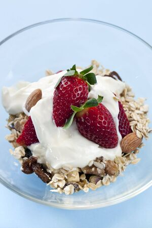 Granola or muesli, topped with strawberries and creamy yoghurt.  Healthy, delicious eating. photo