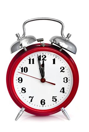 clock hand: Old red alarm clock, showing two minutes to midnight.  Isolated on white.