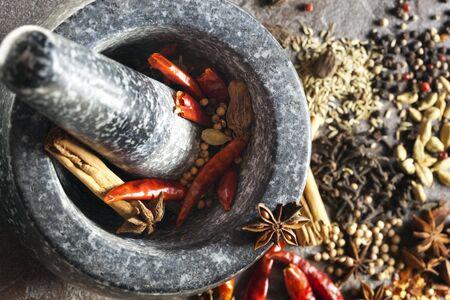 finocchio: Granito mortaio e pestello con spezie pronti per la molatura. Perfetto per rendere garam masala. Include il peperoncino rosso essiccato, cannella, pepe in grani, cardamomo, coriandolo, chiodi di garofano, anice stellato e finocchio.  Archivio Fotografico
