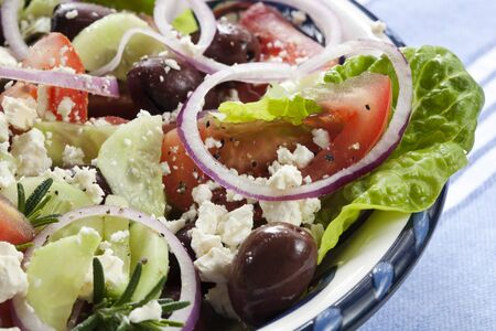 Close-up of bowl of Greek salad.  Luscious vine-ripened tomatoes, with feta cheese, kalamata olives, cucumber, red onion, kos lettuce and rosemary. photo