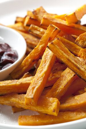 ovenbaked: Oven-baked sweet potato fries, with a dipping sauce.   Stock Photo