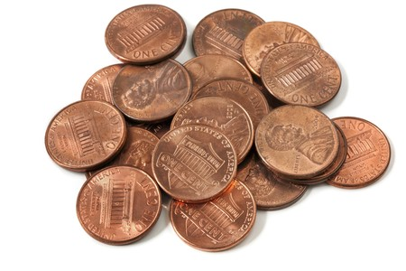 Pile of US one cent coins, over white background.