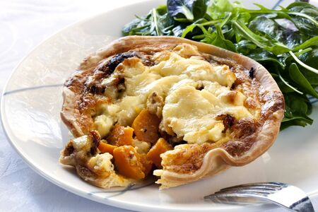 Delicious pumpkin and feta cheese quiche with sundried tomato, served with salad leaves. Stock Photo - 7618593