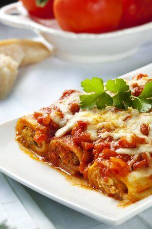 comida italiana: Deliciosos Canelones con una salsa de tomate ricos, cubierto con queso de fusi�n.  Foto de archivo