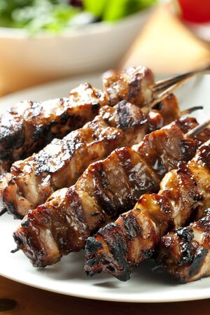hoisin: Barbecued chicken kebabs on a platter, with salad behind.  Delicious! Stock Photo