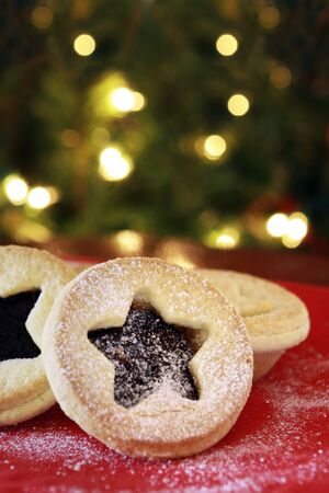 minced pie: Christmas mince pies with blurred fairy lights behind.  A traditional treat for Santa! Stock Photo
