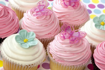 Lots of fancy cupcakes.  Frosted in pink and white, and topped with flowers and butterflies.  Pastel tones. photo