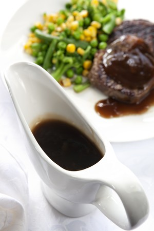 jugs: Gravy boat with steak dinner behind.  Focus on gravy boat.