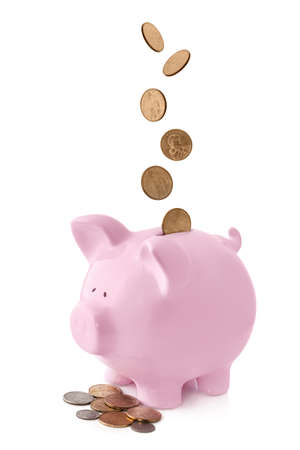 Pink piggy bank, with coins falling into slot.  Isolated on white. photo