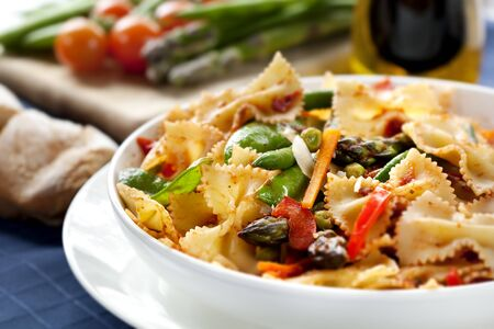primavera: Pasta primavera.  Fresh bow-tie pasta with asparagus, beans, peas, snow-peas, tomatoes, carrots and peppers. Stock Photo