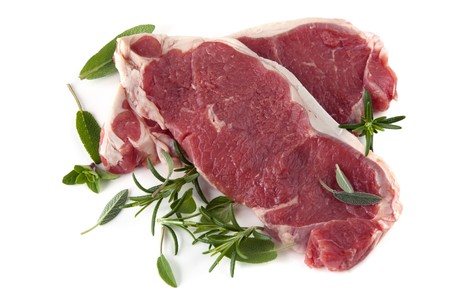 Raw sirloin steaks, with fresh herbs including rosemary, sage and oregano.  Isolated on white. Stock Photo - 7744008