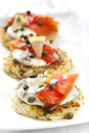 capers: Potato latkes or rostis, topped with smoked salmon, sour cream, capers and red onion. Stock Photo