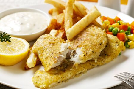 Fish and chips with vegetables, lemon and tartare sauce. photo